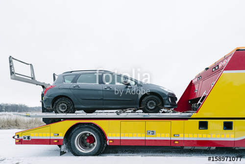 Gray car on tow truck against sky during winter